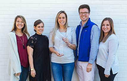 TriMark employees with an SEO award in front of the TriMark office