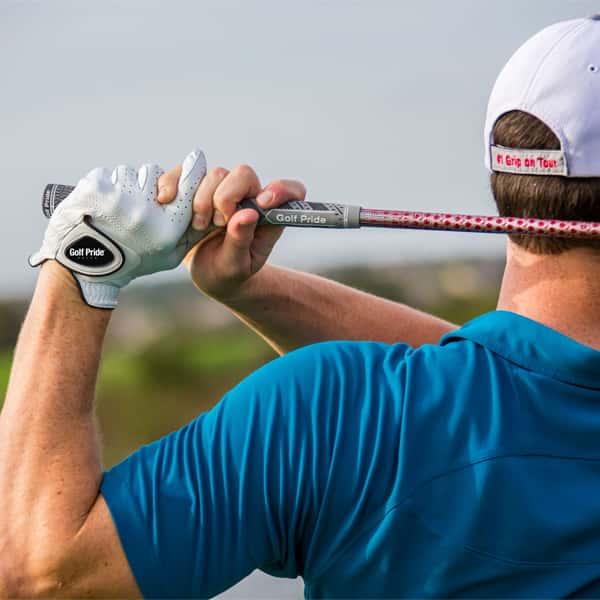 Golfer finishing his swing while using Golf Pride grips