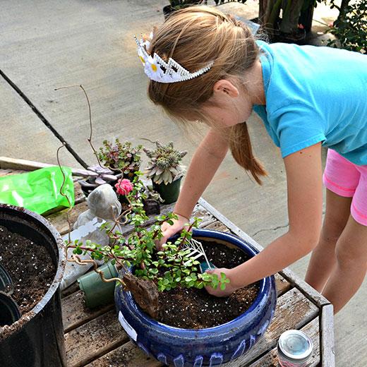 Young girl making a Fairy Garden